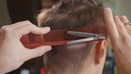 Close-up of barber cuts the hair by scissors at barbershop.