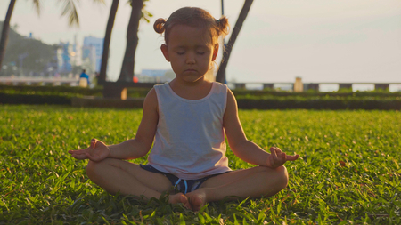 Little cute girl meditates in turkish pose in the park at sunset Stock fotó