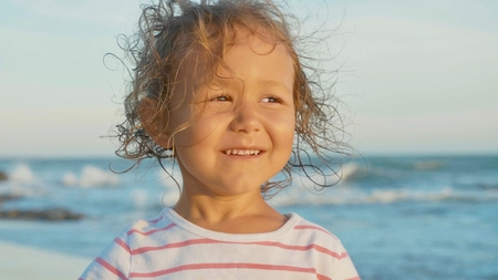 Facial portrait of beautiful little girl standing on the beach and smiling