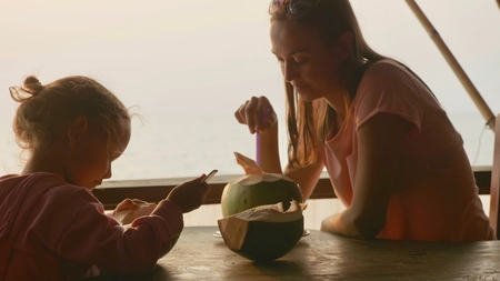 Mother and daughter sits at seaview cafe with coconuts Stock Photo