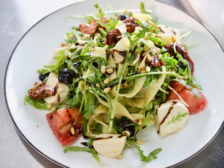 Italian salad with macaroni, cheese, tomato and herbs on the white plate. Stockfoto