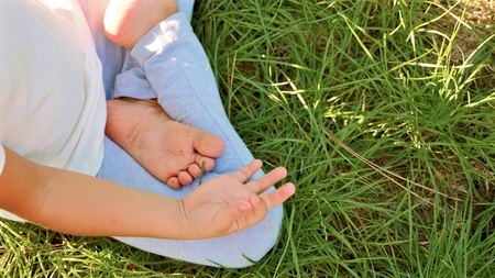 Little cute baby girl meditates on the grass at green summer park.