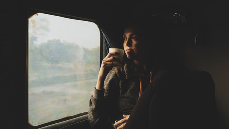 Young women drinking water while looking out of a asian train window