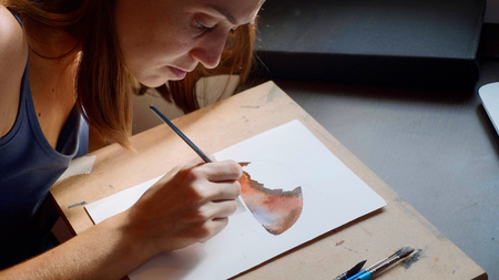 Young woman painting mashroom in watercolor at home Imagens
