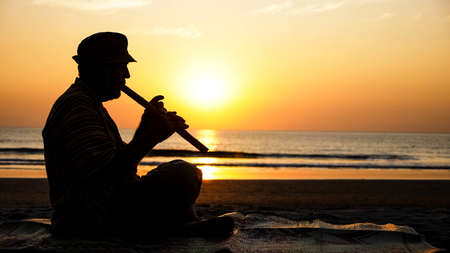 Silhouette of senior man playing bamboo flute on the beach at sunset