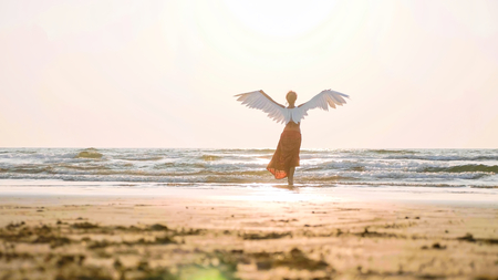 Beautiful female angel walking barefoot toward the sea at sunset.