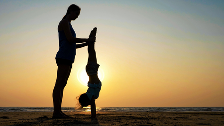 Silhouette of mother with daughter doing gymnastic on the beach at sunset