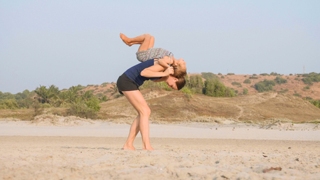 Young sporty mother with little daughter doing gymnastic on the beach.