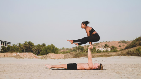Fit sporty couple practicing acro yoga with partner together on the sandy beach. Banque d'images