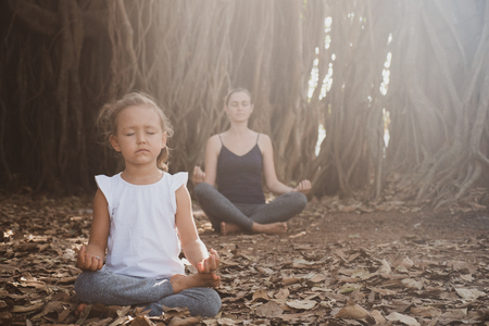 Little child girl with young mother meditating together under banyan tree Foto de archivo - 121094219