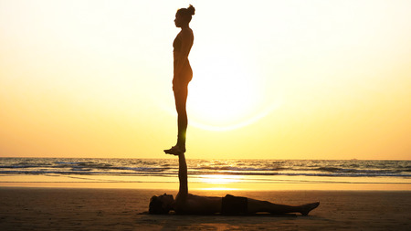 Fit sporty couple practicing acro yoga with partner together on the sandy beach. Stock Photo