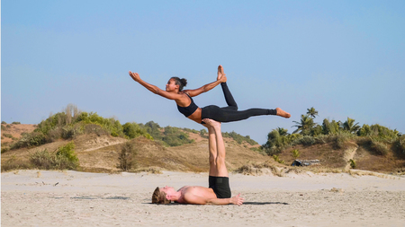 Fit sporty couple practicing acro yoga with partner together on the sandy beach. Stockfoto