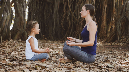 Little child girl with young mother meditating together under banyan tree Imagens