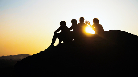 Silhouette group of people admiring the sunset on top of mountain Imagens