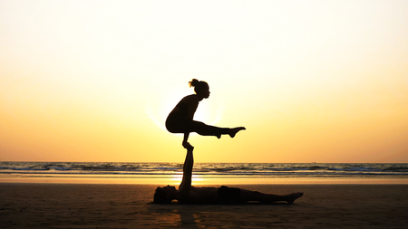 Fit sporty couple practicing acro yoga with partner together on the sandy beach. Imagens