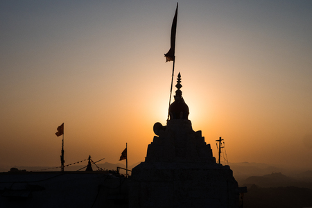 Silhouette roof of temple placed on top of mountain, against the sun at sunrise