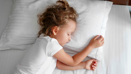 Little cute girl is sleeping in bed at the morning.