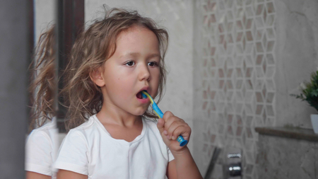 Little child girl is brushing her teeth with toothbrush in bathroom.