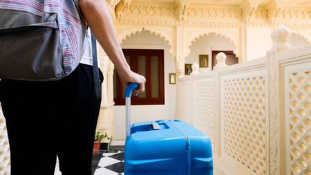 Woman checks into the hotel and rolls the suitcase to her room.