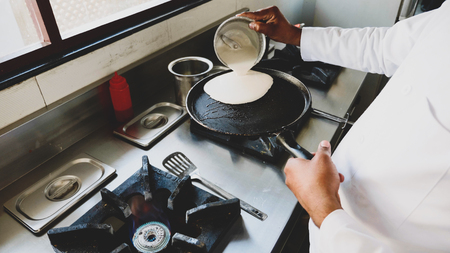 Chef is cooking pancakes on a frying pan in restaurant on gas stove.