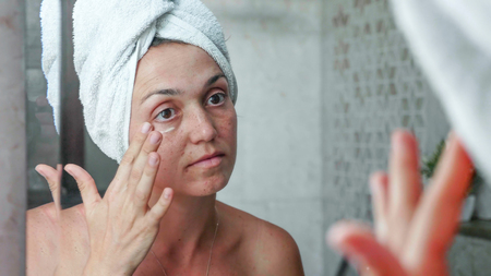 Young woman is applying cream on the face eye area while looking at mirror.