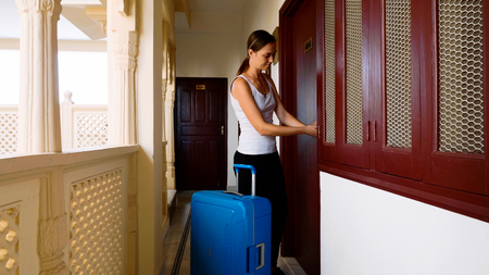 Woman passes into the hotel and rolls the suitcase to her room.
