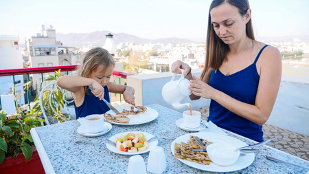 Family are having a breakfast together on terrace with beautiful mountains view