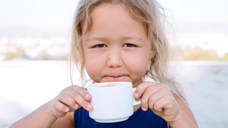 Little blonde girl is drinking cocoa from the white cup.