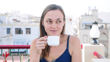 Portrait of woman drinking hot beverage while having a breakfast on terrace.