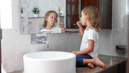 Little kid girl is brushing her teeth with toothbrush in front of the mirror. Imagens