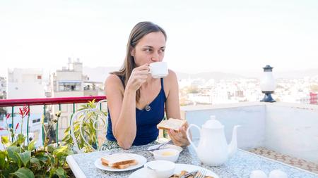 Portrait of woman having a breakfast in cafe on terrace. Imagens