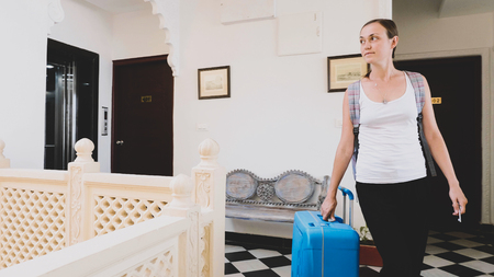 Young woman with suitcase check-in to the hotel.
