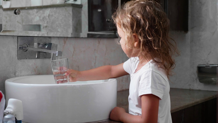 Little girl in bathroom with glass preparing for rinses her mouth with water.