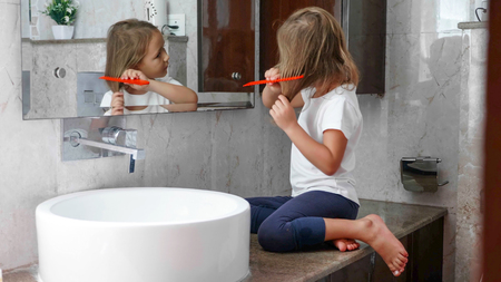 Small blonde girl is combing her hairs in front of the mirror in bathroom. Imagens