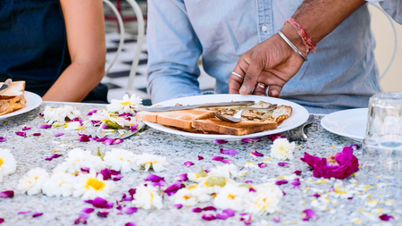 Waiter brings breakfast to a couple sitting at the table covered with flowers.