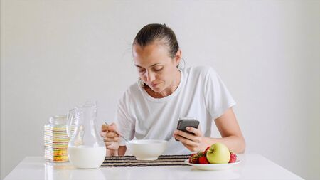 Young woman is having a breakfast and looking in smartphone.