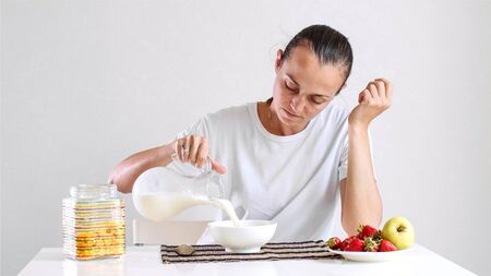 Young woman is having a breakfast cornflake with milk and fruits. Imagens