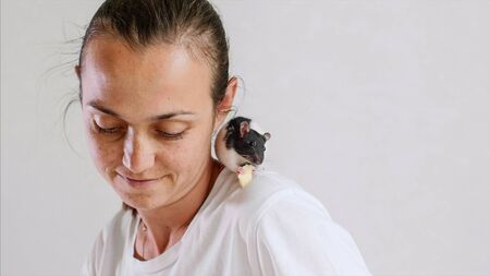 Young woman and pet rat sitting on her shoulder are having a breakfast together.