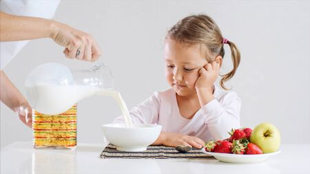 Little girl is waiting her breakfast cornflakes with milk.