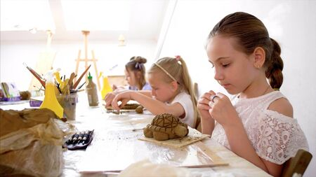 Lesson in art workshop in elementary school. Kids are modeling toys from clay
