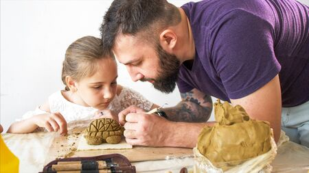 Teacher explains and shows his pupil girl how to modeling a toy from clay.