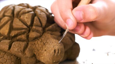 Child is scratching the texture of the scales on handmade turtle toy from clay