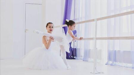 Ballet teacher is teaching little girl to stretch legs near the barre stand.