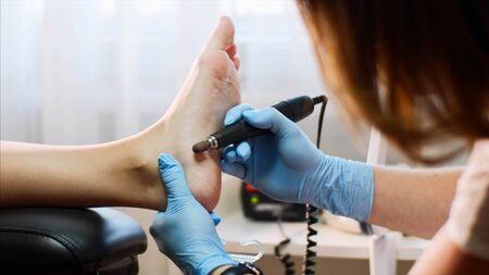 Pedicurist master removes old skin on clients heel making hardware pedicure. Stok Fotoğraf