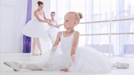 Child girl ballerina in white tutu is doing stretch exercises on ballet lesson.
