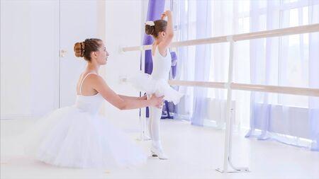 Ballet teacher is teaching little girl near the barre stand. Stok Fotoğraf