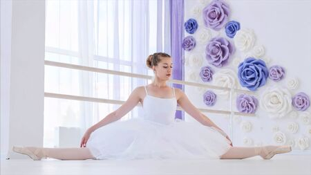 Ballerina in white tutu and pointes stretches sitting on twine in ballet class.