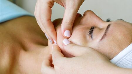 Massage therapist cosmetologist makes facial massage for woman in beauty clinic. Stok Fotoğraf