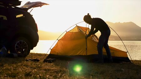 Silhouette of young bearded man sets up a tent at campsite on the lake shore.