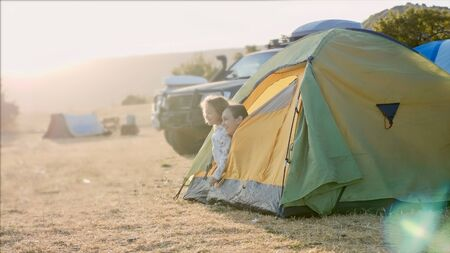 Mother with little daughter wakes up and looks out from tourist tent